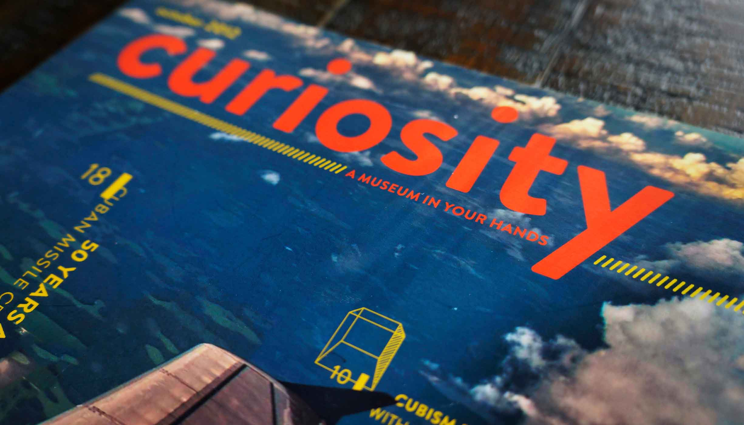 """The cover of Curiosity, featuring its title and tagline, """"A museum in your hands""""."""