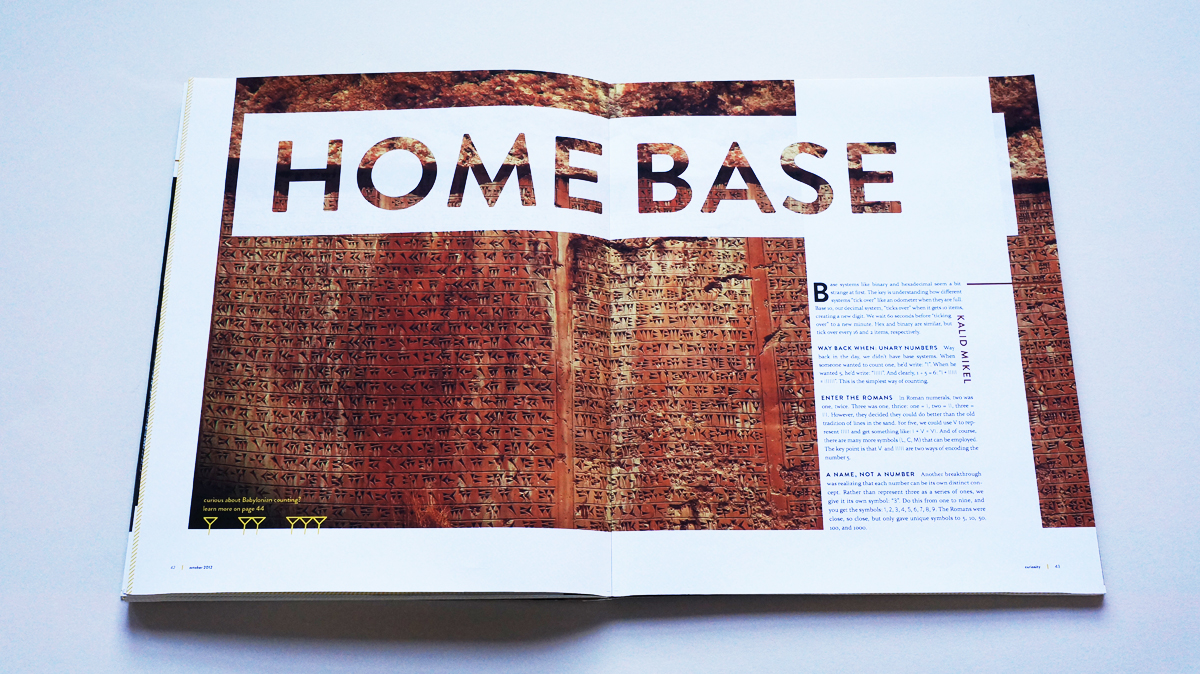 """A red rock wall of Babylonian markings serves as the backdrop for """"Home base""""."""